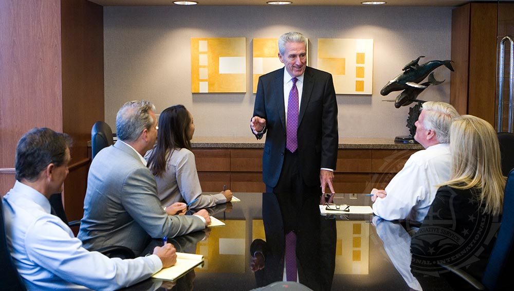 Private investigator Thomas G. Martin addresses a team in the conference room of his Newport Beach office.