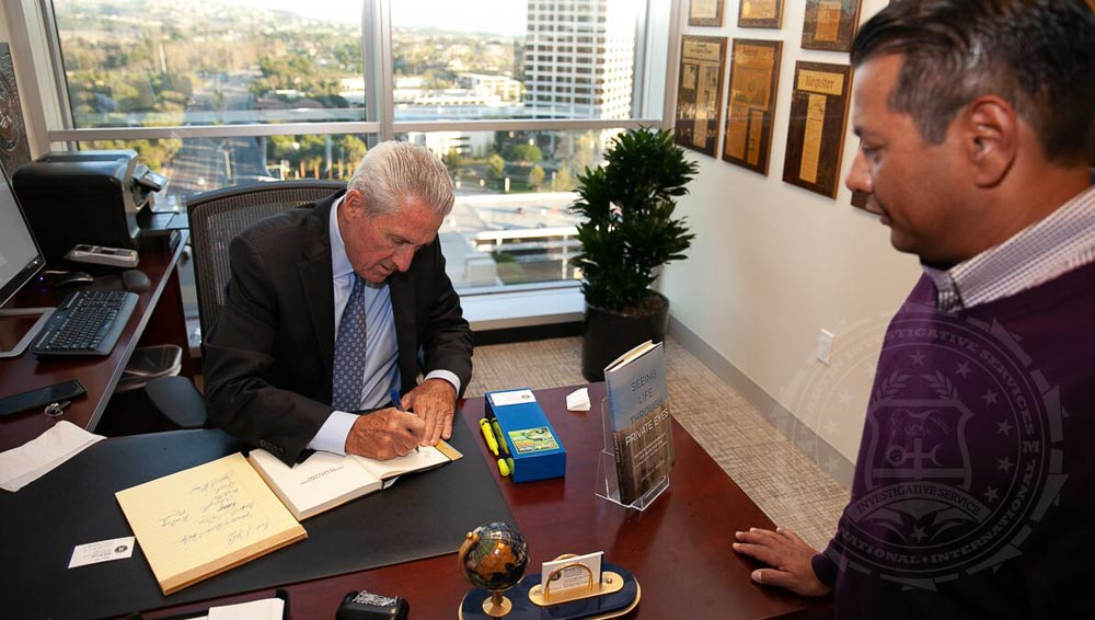 Private investigator Thomas G. Martin signs a copy of his second book, Seeing Life Through Private Eyes.